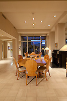 2 round dining tables are seen in large open floorplan home at dusk
