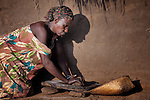 In front of her house, Christine Patina grinds sorghum for food for her family in the morning in Pisak, a village in Southern Sudan. Patina is a United Methodist.
