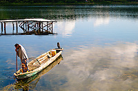 A fisherman in the shallows of Lake Peten Itza next to Flores using a traditional wooden boat and mesh cage.