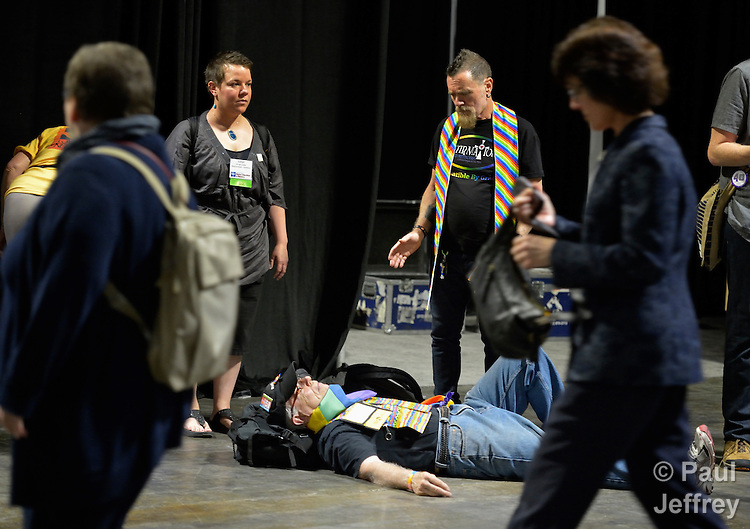 """Demonstrators hold a """"die-in"""" as delegates to the 2012 United Methodist General Conference exit a plenary session in Tampa, Florida. The demonstrators are protesting the church's exclusion of gays and lesbians from full inclusion in the life and leadership of the church."""