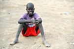 A displaced boy sits on the ground in Agok, a town in the contested Abyei region where tens of thousands of people fled in 2011 after an attack by soldiers and militias from the northern Republic of Sudan on most parts of Abyei. Although the 2005 Comprehensive Peace Agreement called for residents of Abyei--which sits on the border between Sudan and South Sudan--to hold a referendum on whether they wanted to align with the north or the newly independent South Sudan, the government in Khartoum and northern-backed Misseriya nomads, excluded from voting as they only live part of the year in Abyei, blocked the vote and attacked the majority Dinka Ngok population. The African Union has proposed a new peace plan, including a referendum to be held in October 2013, but it has been rejected by the Misseriya and Khartoum. The Catholic parish of Abyei, with support from Caritas South Sudan and other international church partners, has maintained its pastoral presence among the displaced and assisted them with food, shelter, and other relief supplies.