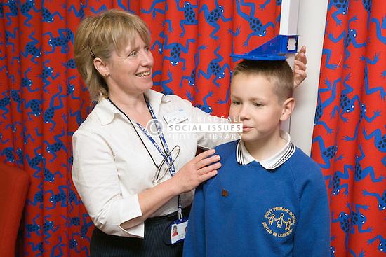 School nurse measuring height of young boy,