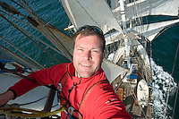 Isle of Skye, Hebrides, Scotland, May 2010. Photographer Frits Meyst in the top of the mast.  Raising the sails requires high altitude acrobatics. From the mast one gets an impressive aerial view over the ship. Tallship Thalssa cuts through the water under full sail. Dutch Tallship Thalassa sails between the islands along the Scotish west coast in search of the quality single malt whisky that is produced by the many distilleries. Photo by Frits Meyst/Adventure4ever.com