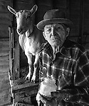 """December 1971:  Modesto, California—Dad Walkling—Dad greets the new year with Goat milk from Brigette.  I first met Orlando """"Dad"""" Walkling at his house in the airport district of Modesto just before his 104th birthday.  Walkling was born in Indian Territory January 2, 1868, near a town now called McAlester, Oklahoma.  His mother was Shawnee and his father, whom he didn't remember, was an Englishman named Orlando.  He later used the name Walkling instead of his Indian name of Skipocase.  On September 16, 1893, Skipocase O. Walkling, then 25 years old, was among thousands of settlers who rode into the Cherokee Strip Land Run of Oklahoma to make a free land claim.  Walkling told of how he rode into the 226-mile long """"Strip"""" to claim 160 acres.  """"There were thousands of men who waited at the line until noon that day.  The army gun was fired and chaos broke out. Every man carried a gun. There was no law, no sheriff, nothing.  People had to fight for their claim even though they were first.""""  Walkling made a claim, but later gave it up when he had a chance to farm a piece of land in Noble County, Oklahoma.  He cleared the land with six yoke of oxen and planted peach orchards.  He and his first wife ran a combination grocery store and hotel there.  He had nearly 1,000 trees and began a cannery to process the crops.  """"One day when the train came in a woman dressed like a Salvation Army woman handed me a bundle as I stood on the ramp, then she jumped back into the train.  I opened it and there was a pair of twins, a boy and a girl,"""" Walkling said.  He and his wife did not have children, so they adopted the twins legally and raised them.  He said they raised six others but did not adopt them.  He came to Modesto in 1944 at 76 years of age and went to work for a meat firm before he opened a poultry store.  After that store closed, he made bullwhips and wove rope for truckers at his home.  In 1968, Dad Walking, then 100 years old, visited Oklahoma for the 75th anniver"""