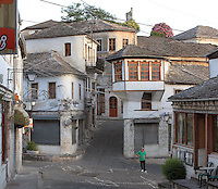 The Qafe or Neck of the Bazaar, a busy intersection of 5 streets that forms the heart of the old town of Gjirokastra, Southern Albania. Most of the Ottoman houses date from the 17th and 18th centuries. Gjirokastra was settled by the Greek Chaonians, the Romans and Byzantines before becoming an Ottoman city in 1417. Its old town was listed as a UNESCO World Heritage Site in 2005. Picture by Manuel Cohen