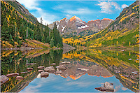 From the iconic Maroon Bells, this Colorado image was captured on a cool fall morning. The first light of day gently warms Maroon Peak and North Maroon Peak, two of Colorado's 14ers. In the shadow of these peaks rests Maroon Lake.