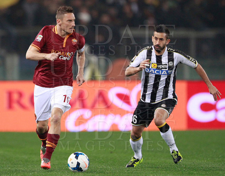 Calcio, Serie A: Roma vs Udinese. Roma, stadio Olimpico, 17 marzo 2014.<br /> AS Roma forward Francesco Totti is chased by Udinese midfielder Giampiero Pinzi, right, during the Italian Serie A football match between AS Roma and Udinese at Rome's Olympic stadium, 17 March 2014.<br /> UPDATE IMAGES PRESS/Isabella Bonotto