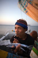 September 9th 2007- Bali, Indonesia- A fisherman holds some small fish in his hand while smoking a cigarette on the beach in front of a dive site known as Jemeluk Bay, which is located near the Amed area of North East Bali. The area around Amed is very dry and not suitable for rice, so the local population depends heavily on the tourism trade. That has helped the dive operators ink deals with local villagers to protect the in-shore reefs, with fishermen promising to drop their lines out at sea. The dive shops pay monthly dues to the villages and pay to use local porters to carry tanks and boats to reach the sites. Photograph by Daniel J. Groshong/Tayo Photo Group