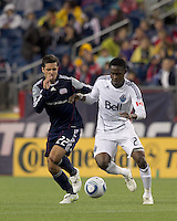 Vancouver Whitecaps FC midfielder Gershon Koffie (28) dribbles as New England Revolution forward Benny Feilhaber (22) pressures. In a Major League Soccer (MLS) match, the New England Revolution defeated the Vancouver Whitecaps FC, 1-0, at Gillette Stadium on May14, 2011.