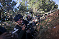 In this Saturday, Dec. 15, 2012 photo, Syrian rebel fighters take a breath as they wait to enter in combat inside a trench during heavy clashes inside one militar academy besieged by rebels at the north of Aleppo, Syria. The Free Syrian Army took control over the Academy after several hours battling the troops loyal to President Bashar al-Assad. Among the casualities are one FSA General and one Syrian journalist. (AP Photo/Narciso Contreras)