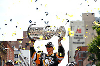 Sidney Crosby #87 of the Pittsburgh Penguins hoists the Stanley Cup for the crowd during the victory parade in downtown Pittsburgh, Pennsylvania on June 15, 2016. (Photo by Jared Wickerham / DKPS)
