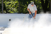 NWA Democrat-Gazette/DAVID GOTTSCHALK  Eric Larson, a maintenance II worker with the city of Fayetteville Parks and Recreation Department, uses May 15, 2017, a floor disc on the end of a power washer to clean the bottom of the Wilson Park Pool in Fayetteville. Larson was working with Jesse Rose, a temporary worker, on the that will be open Saturday, June 3, through Sunday, August 13.