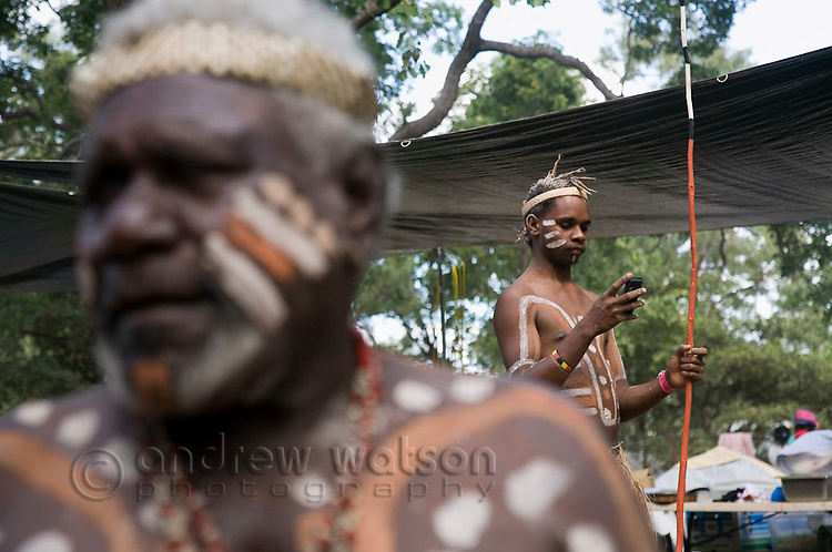 A young indigenous dancer checks his mobile phone at the Laura Aboriginal Dance Festival.  Laura, Queensland, Australia