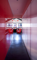 One side of a long corridor leading to the master bedroom is panelled in bright red lacquer and the other in transparent acrylic to allow in daylight