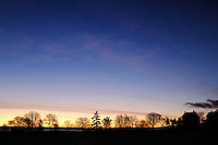 Trees and house silhouetted against sunrise, Fort Worden State Park, Port Townsend, Washington, USA