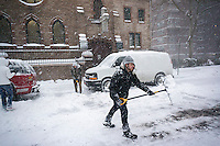 People shovel out their cars in Chelsea in New York during Winter Storm Jonas on Saturday, January 23, 2016. New York has issued a traffic ban prohibiting driving private vehicles on the city's streets. (© Richard B. Levine)