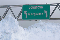 Highway signs for the cities of Marquette, Munising and Escanaba in the Upper Peninsula of Michigan in winter with snow piles.