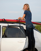 woman tying a paddle board to her car rooftop