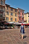 A woman wearing a blue dress and a red straw walks towards the famous Vanini cafe, that sits on the main piazza/plaza in Lugano, Switzerland