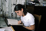 Berkeley CA Girl, 17, reading book while working on school paper on computer at home  MR