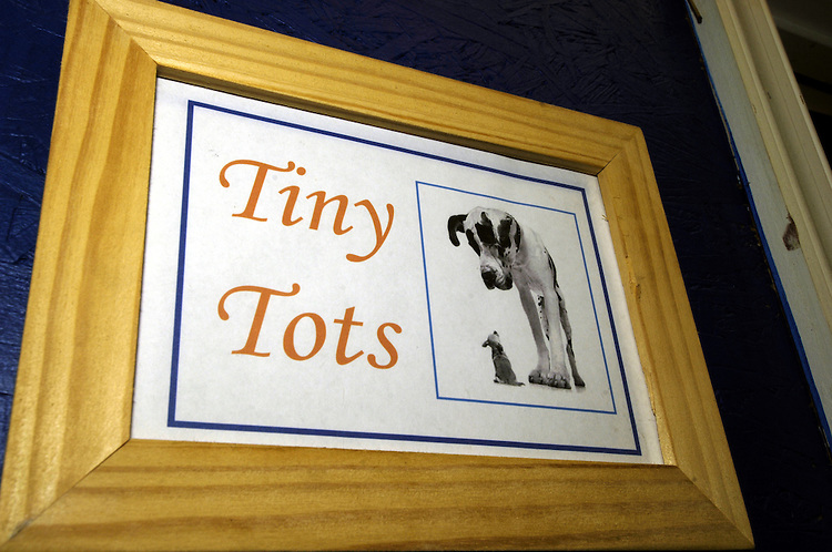 A sign for small breeds room at Wag Time reads tiny tots room.