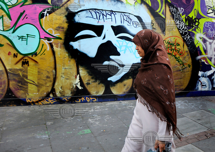 Muslim woman passing graffiti on a closed down curry house by Brick Lane, which has become the heart of the city's Bangladeshi community.