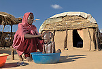 Fatna bathes and dresses her son Mustafa in a camp for internally displaced persons outside Kubum, in South Darfur.