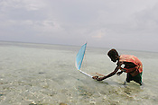 A young boy releases his model wooden canoe and outrigger into the lagoon, on the beach of Iangain Island, on the Carterets Atoll, Papua New Guinea, on Tuesday, Dec. 12, 2006.  Rising sea levels have eroded much of the coastlines of the low lying Carteret islands (situated 80km from Bougainville island, in the South Pacific), and waves have crashed over the islands flooding and destroying what little crop gardens the islanders have. Food is in short supply, banana and swamp taro crops are failing due to the salt contamination of the land, and the islanders live on a meagre one meal per day diet of fish and coconut. There is talk by the Autonomous Region of Bougainville government to relocate the Carteret Islanders to Bougainville island, but this plan is stalled due to a lack of finances, resources, land and coordination.