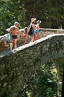 Kobarid, Soca Valley, Julian Alps, Slovenia, July 2012. Swimmers and kayakers enjoy the cooling water of the Nadiza river under the Napoleon Bridge. Slovenia boasts a very spectacular carstic landscape with high limestone rock formations oozing with waterfalls, and fast flowing cristal clear waters that run through the Soca from the Triglav National Park to the Adriatic Sea. The Julian Alps are a paradise for outdoor adventure and adrenaline sports. The 3 centers for all activities are Bovec, Kobarid and Tolmin. Photo by Frits Meyst/Adventure4ever.com