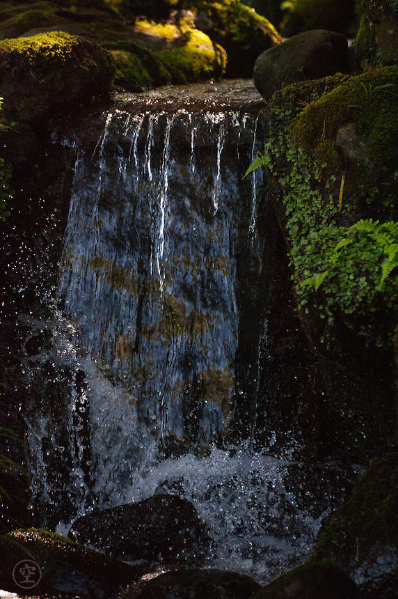 A waterfall along a landscaped creek in Kenrokuen Garden is beautifully and deceptively natural.