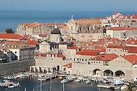 The old harbour developed by architect Paskoje Milicevic in the 15th century, and the medieval walled city behind, Dubrovnik, Croatia. The city developed as an important port in the 15th and 16th centuries and has had a multicultural history, allied to the Romans, Ostrogoths, Byzantines, Ancona, Hungary and the Ottomans. In 1979 the city was listed as a UNESCO World Heritage Site. Picture by Manuel Cohen