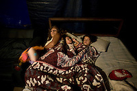 Elizabeth, co-owner of the Jhon Danyer Circus, in bed with her two daughters Yesica and Vanesa in the temporary tent. Around a dozen small circuses wander the poorer neighbourhoods around the city of Medellin putting on performances in what can be a hand to mouth existence. Despite falling audience numbers, new health and safety regulations and other bureaucracy these small family businesses, many of whom have existed for generations, still scrape a living in a world where the people are more accustomed to being entertained by soap operas than by live entertainment...