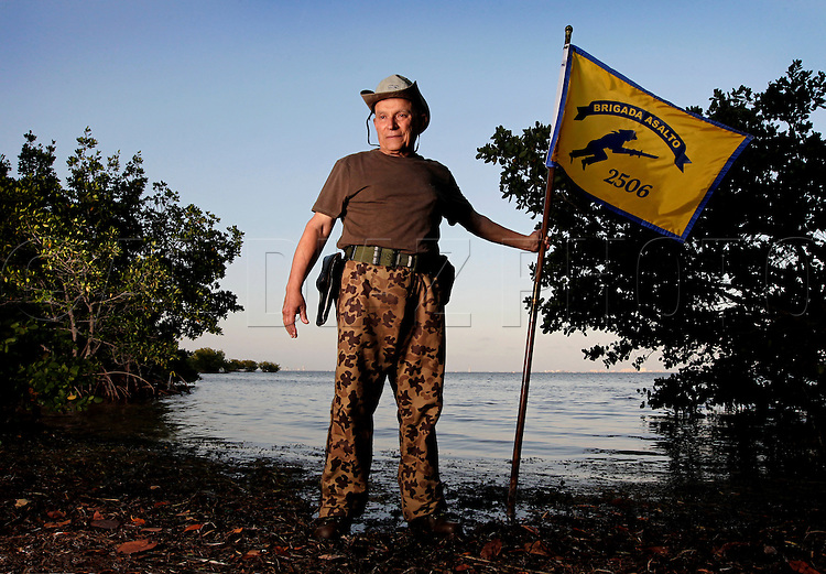Mario Martinez-Malo is a member of the Bay of Pigs Veterans Association, Brigade 2506. Here he poses with the 2506 Brigade flag on March 30, 2011.
