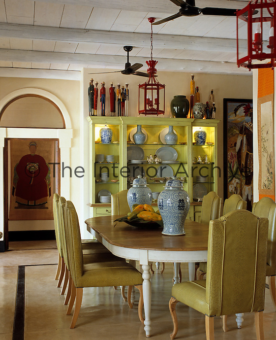The dining room of a country house hotel in Africa is decorated in a Chinese theme with a collection of blue-and-white ceramics displayed against the mimosa-yellow of a painted antique cabinet