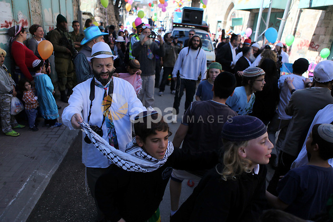 Israeli settlers dance during celebrations marking the Jewish holiday of Purim in the occupied West Bank city of Hebron March 5, 2015. Purim is a celebration of the Jews' salvation from genocide in ancient Persia, as recounted in the Book of Esther. Photo by Mamoun Wazwaz