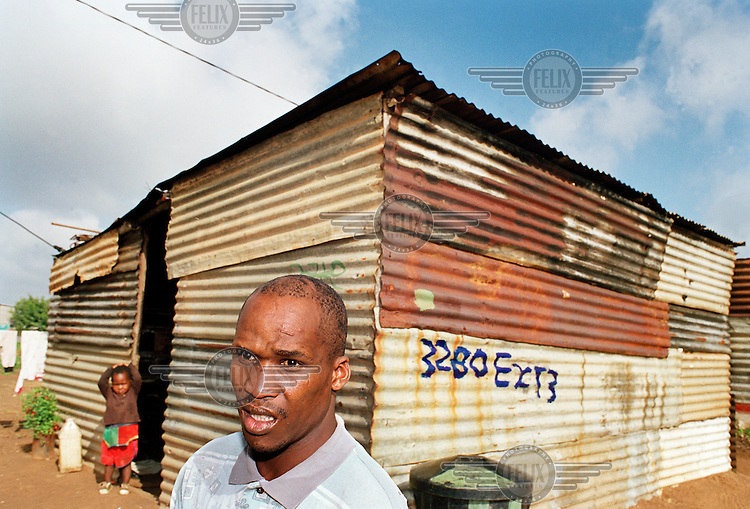 Paul Motshabi and his child stand outside their home. In 1996 Motshabi was left brain damaged after being attacked by his employer, Eugene Terre'Blanche, leader of the Afrikaner Weerstandsbeweging (AWB - Afrikaner Resistance Movement). Terre'Blanche was sentenced to six years for attempted murder.