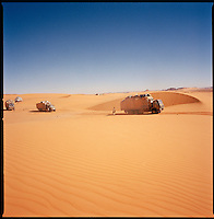 Sahara desert, Libya-Chad, November/December 2004..Every week, a convoy of 40 privately owned Libyan trucks loaded by the WFP with about 1000 metric tons of western food aid cross 2500 km of deep desert across Libya and Chad to reach more than 200 000 refugees from Darfur in camps near the Sudanese border. The convoy crossing a very difficult sand dunes patch; each truck carrying 25 metric tons of food aid plus his gasoil and supplies weighs about 40 metric tons; it sinks deeply in the soft sand...