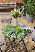 Cut flowers from the garden for arranging in a rustic vase, on wooden table, bench, pebble mulch, roses, Alchemilla lady's mantle, Ammi, etc, mixed flowers