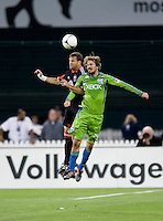 Daniel Woolard (21) of D.C. United goes up for a header with Roger Levesque (24) of the Seattle Sounders during the game at RFK Stadium in Washington DC.   D.C. United tied  the Seattle Sounders, 0-0.