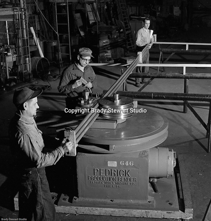 Client: The Pittsburgh Piping Company<br /> Ad Agency:<br /> Product: Fabricated Steel Pipe<br /> Location: On location<br /> <br /> View of operator and two assistants bending pipe with the new Pedrick Production Bender machine.  The manufacturer is the Pedrick Tool &amp; Machine Company of Philadelphia Pennsylvania.