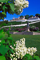 LILACS FRAME A STATUE OF FATHER JACQUES MARQUETTE ON THE LAWN BELOW FORT MACKINAC ON MACKINAC ISLAND, MICHIGAN.