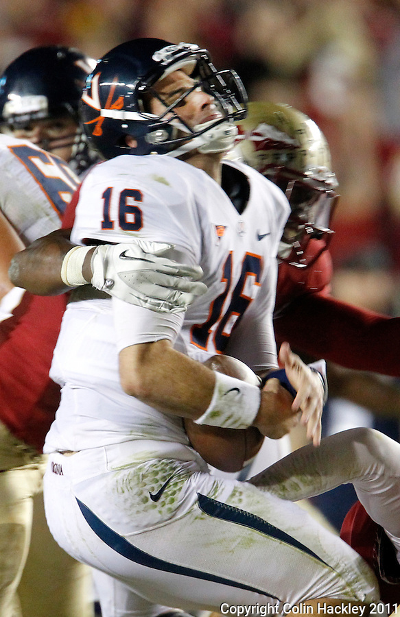 TALLAHASSEE, FL 11/19/11-FSU-UVA111911 CH-Florida State's Brandon Jenkins snaps the head of Virginia's Michael Rocco back during first half action Saturday at Doak Campbell Stadium in Tallahassee. .COLIN HACKLEY PHOTO
