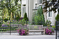 Wooden garden benches and ornamental planters in a garden courtyard.