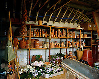 Terracotta plant pots of all sizes stand stacked on the shelves which line the walls of this garden shed