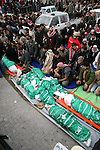 The bodies of two of the children of Hamas leader Nizar Rayan, who was killed Thursday in an Israeli airstrike with 4 of his wives and 10 of his children is lowered into a grave during their funeral in the town of Beit Lahiya, northern Gaza Strip,  APAIMAGES PHOTO / Ashraf Amra