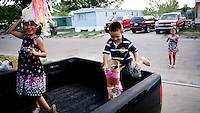 Children play in a trailer park in Garden City, Kansas. The area is home to many migrant workers who have come to the town to work at the Tyson meat packing plant. The Tyson facility kills and processes between five and six thousand beef cattle every day. Kansas dominates the American beef industry, producing 25% of all beef raised in the USA. However, the industry is heavily dependent on cheap immigrant labour.