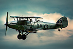 A 1935 Hawker Hind flying on a cloudy day