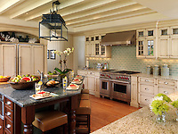 A coastal kitchen with beachy washed wood-finished cabinetry and lantern lit breakfast island.