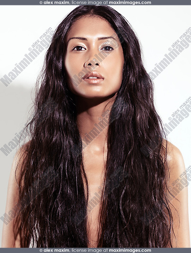 Expressive artistic beauty portrait of a beautiful young exotic woman with very long wavy brown hair, front view on white background