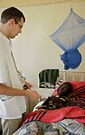 Foto: VidiPhoto..MASVINGO - Topdrukte in het missieziekenhuis Morgenster in Masvingo Zimbabwe. Omdat er nauwelijks medicijnen voorhanden zijn en veel staatsziekenhuizen nog plat liggen vanwege stakingen, krijgen de missieziekenhuizen in Zimbabwe te maken met een enorme golf aan patiënten uit de wijde regio. Zo ook het missieziekenhuis Morgenster bij Masvingo, dat gerund wordt door de Nederlandse arts Herman ten Hove. Het ziekenhuis wordt onder meer financieel gesteund door de Nederlandse zendingsorganisatie GZB. Foto: Herman ten Hove onderzoekt een vrouw met aids.